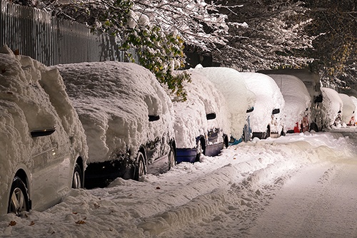 A number of parked cars covered in snow.